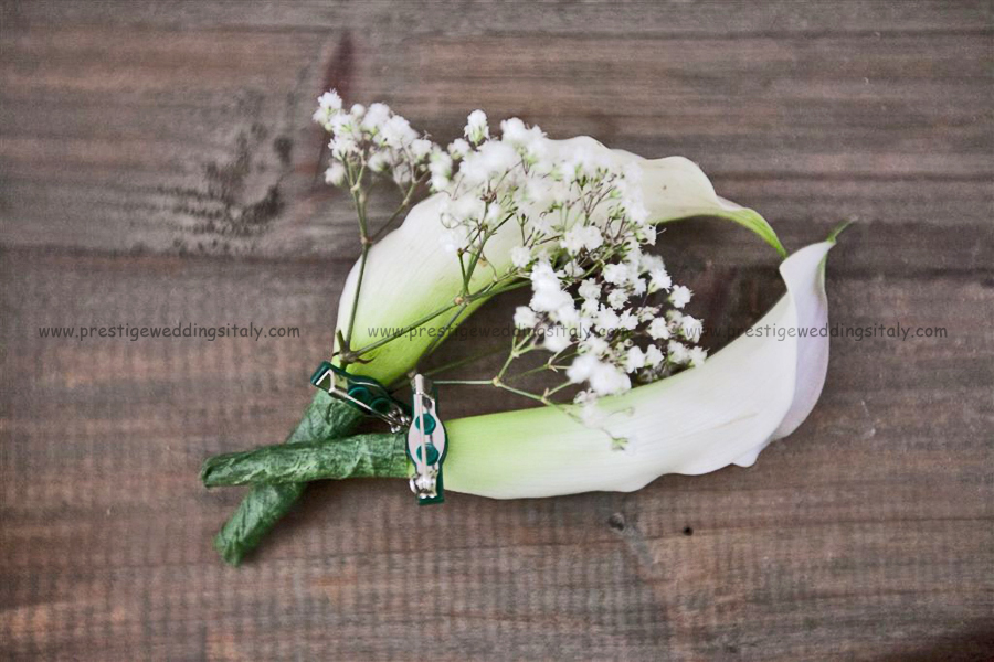 Buttonholes for wedding in Italy with calla lilly and baby breath, steam with green paper ribbon. This buttonhole is perfect for calla lilly bride bouquet.